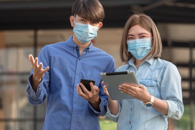 아시아 사람들은 안면 마스크를 쓰고 태블릿을 사용합니다.