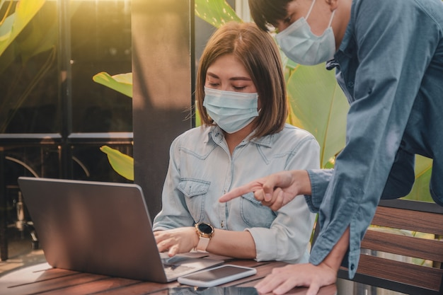 Asian people wear surgical mask freelance working by laptop