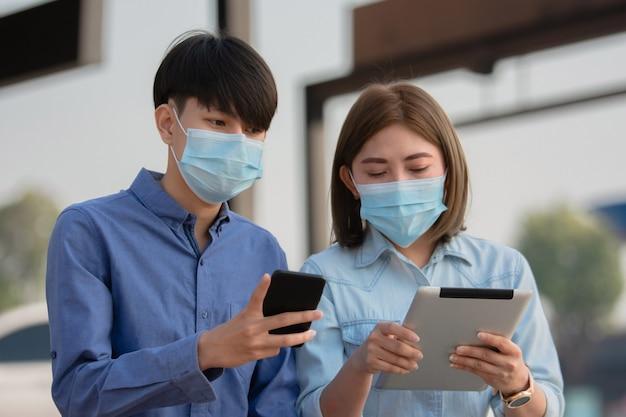 아시아 사람들은 태블릿으로 작업하는 외과 마스크 프리랜서를 착용