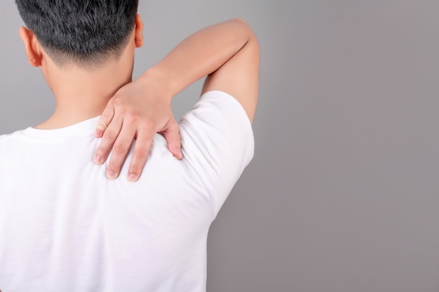 Asian people wear white t-shirts with shoulder pain, using their hands to touch the shoulders on a gray background.