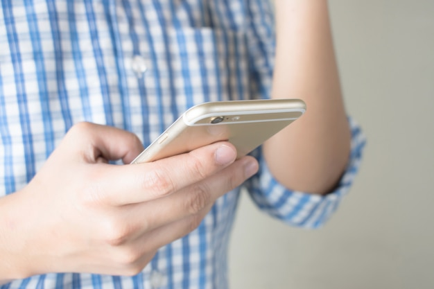Asian people wearing a blue plaid shirt touching the screen on a smartphone. close up to the side view.