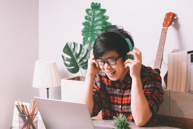Азиатские люди, работающие на ноутбуке и носящие стереогарнитуру, чтобы слушать музыку, работая из дома