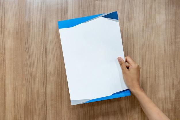 Азиатский человек держит и поднимает пустой лист бумаги формата а4 на деревянном фоне.