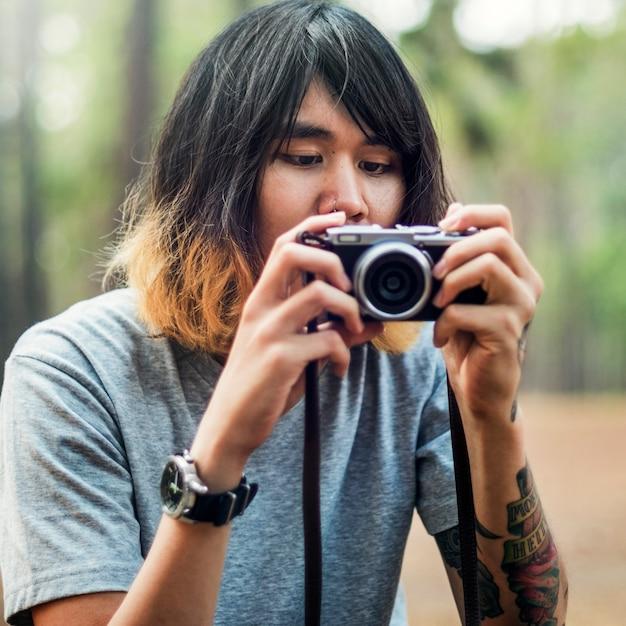 Азиатский фотограф, фотографирующий на открытом воздухе