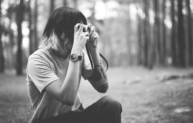 Азиатский фотограф фотографировать на открытом воздухе концепции