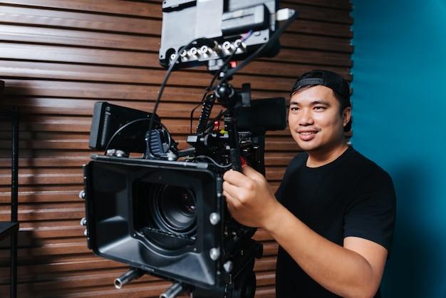 撮影セットに映画用カメラを持っているアジアの写真家。