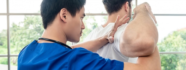 Asian physical therapist stretching athlete male patient shoulder and back in clinic