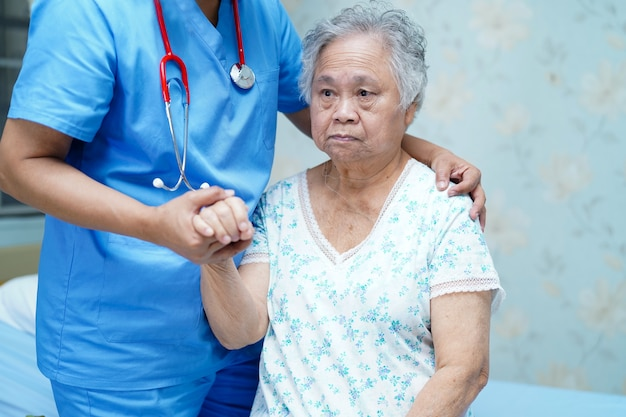 Asian physiotherapist help and support old patient at hospital.