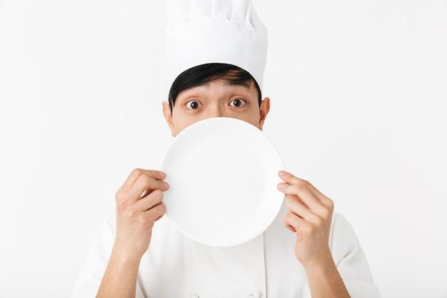 Азиатский довольный главный мужчина в белой форме повара улыбается в камеру, держа тарелку, изолированную над белой стеной