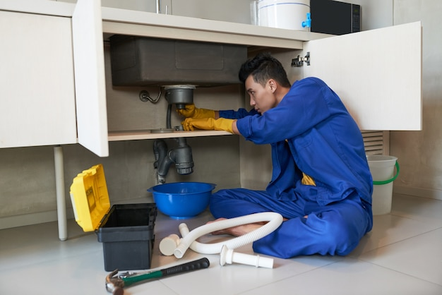 Азиатский сантехник в синем комбинезоне очищает засор в канализации