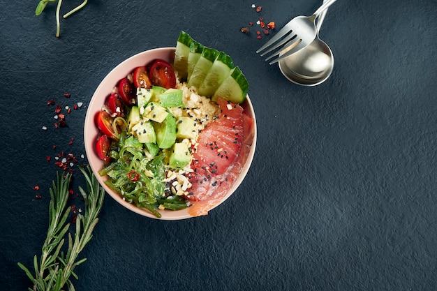 サーモン、アボカド、チェリートマト、キュウリ、ワカメの黒いテーブルのアジア風ポークボウル。おいしいダイエット食品。トップビューとコピースペース付きのフラット