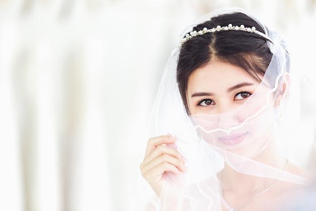 Asian portrait of cute lady smiling happy wearing wedding dress