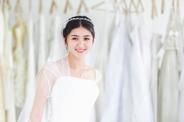 Asian portrait of cute lady smiling happy wearing wedding dress