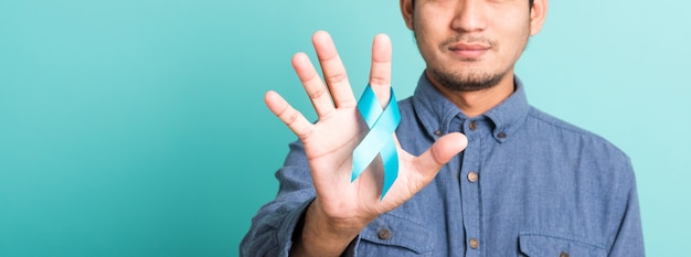 Asian portrait happy handsome man posing he holding light blue ribbon for supporting people living and illness