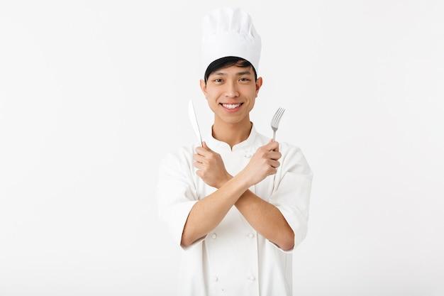 Азиатский позитивный главный мужчина в белой форме повара улыбается в камеру, держа в руках столовые приборы, изолированные на белой стене