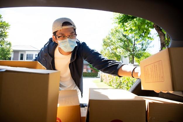 소포 패키지를 줍는 위생 보호용 안면 마스크가 달린 아시아 우체부