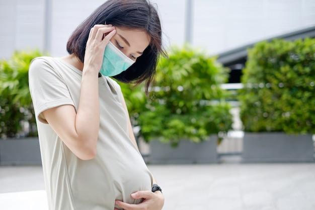 長いドレスを着たアジアの妊娠中の母親は頭痛を抱えており、頭とお腹を抱えています。