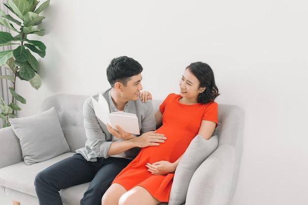 아시아 임신 한 여자와 남편이 소파에 앉아 책을 읽고