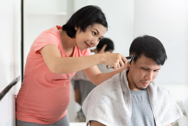 Asian pregnant woman cutting husband hair with clipper at home
