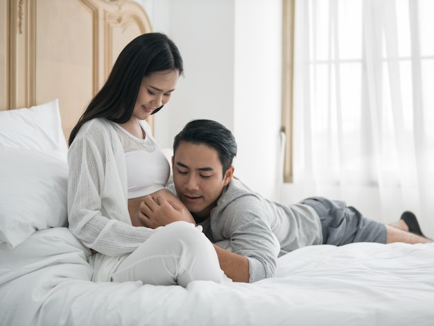 Asian pregnant woman and husband laying on the bed while spending time together