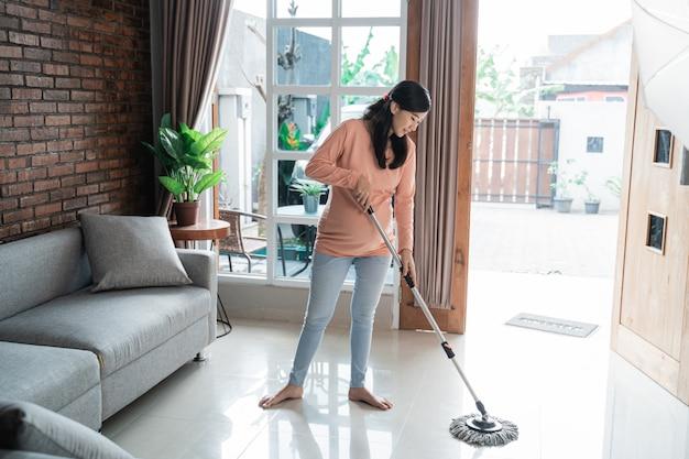 床を拭くアジアの妊娠中の女性