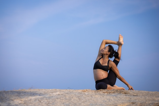 Asian pregnant woman yoga on the beach sunset summer time
