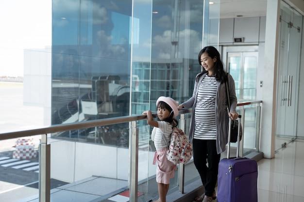 아시아 임산부와 그들의 딸 탑승 대기