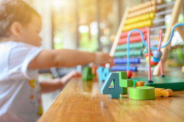 아시아 취학 전 연령은 화려한 장난감으로 혼자 놀고 있습니다. 아이를 위한 교육 게임. 아기 학습과 생활 방식.