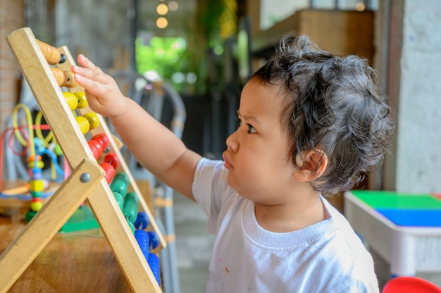 Asian preschool age play with colorful toy alone. education game for kid. baby learning and lifestyle.