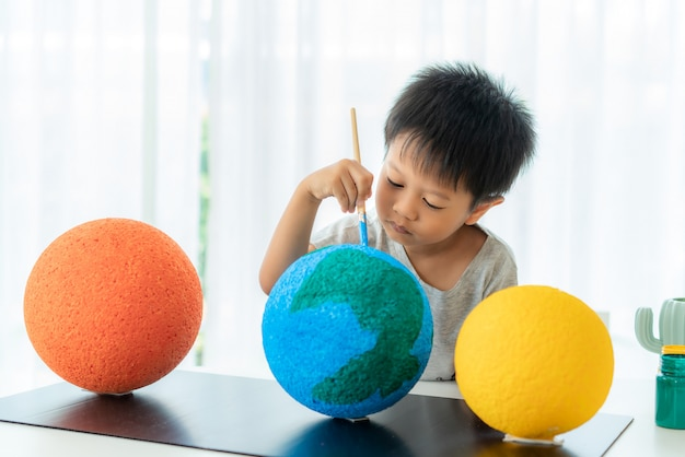 Asian preschool student boy painting the moon learning about the solar system at home,