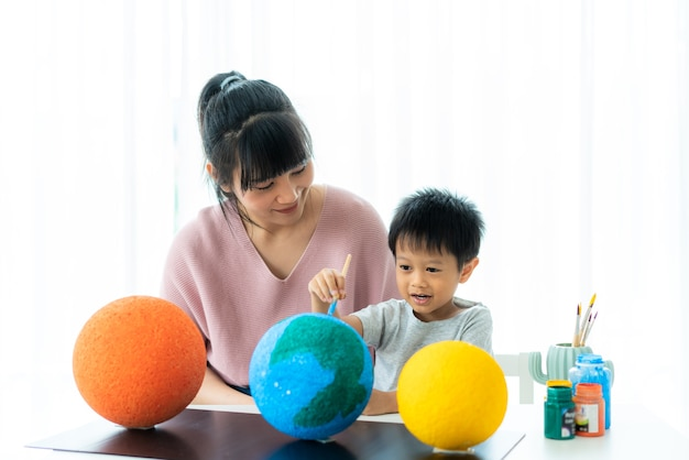 Asian preschool student boy with mother painting the moon learning about the solar system at home
