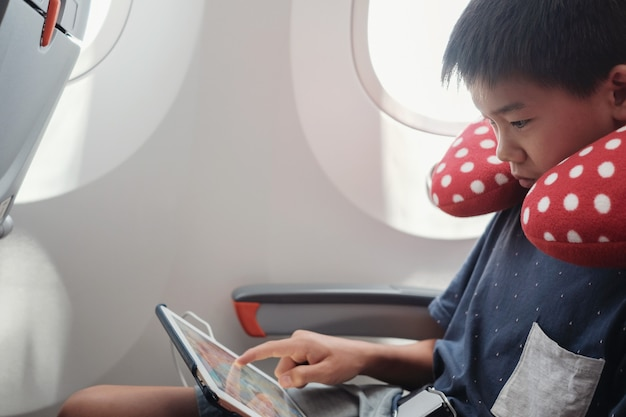 Asian preteen boy using tablet in flight, family traveling abroad with children
