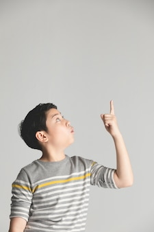 Asian preteen teenage boy points up over gray background.