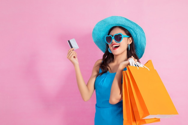 Asian pretty girl holding shopping bags while hold credit cards and sunglasses shopping concept.
