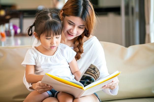 아시아 예쁜 어머니와 그녀의 행복한 딸이 함께 거실에 아늑한 소파에 이야기 책을 읽고