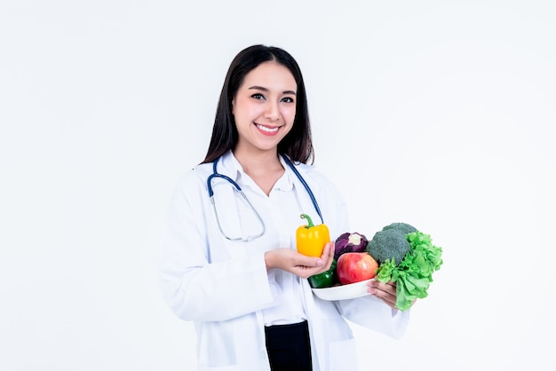 Asian pretty woman doctor, nutritionist holding and showing many fresh vegetables and fruits