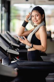 Азиатская симпатичная женщина в спортивной одежде и умных часах отдыхает на беговой дорожке, использует смартфон и приложение для тренировки умных часов и слушает музыку в современном тренажерном зале