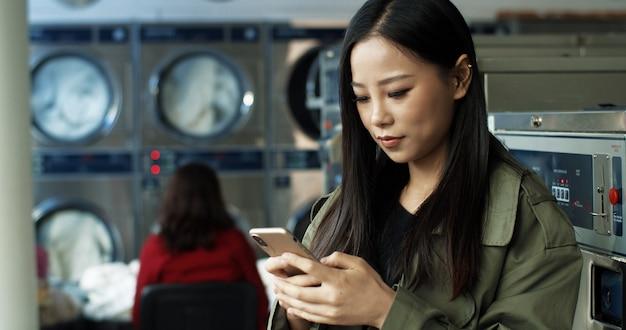 공공 세탁실에 서있는 동안 길고 검은 머리 도청 및 스마트 폰 문자 메시지와 함께 아시아 예쁜 여자. 아름 다운 여자 전화에 입력 하 고 세척 옷을 기다리고 있습니다.