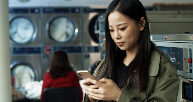 Asian pretty woman with long dark hair tapping and texting message on smartphone while standing in public laundromat. beautiful woman typing on phone and waiting for clothes to wash.