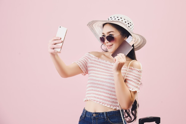 笑顔のアジアのかわいい若い女の子はサングラスを着用し、スマートフォンで自分撮りを取ります、若い女性のバックパッカーは自分撮りを取り、スタジオピンクの背景でパスポートを保持しています。パステルピンクのトーンフィルター。