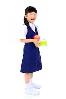 Азиатская девочка начальной школы, держащая ланч-бокс. концепция здорового питания для школьника.