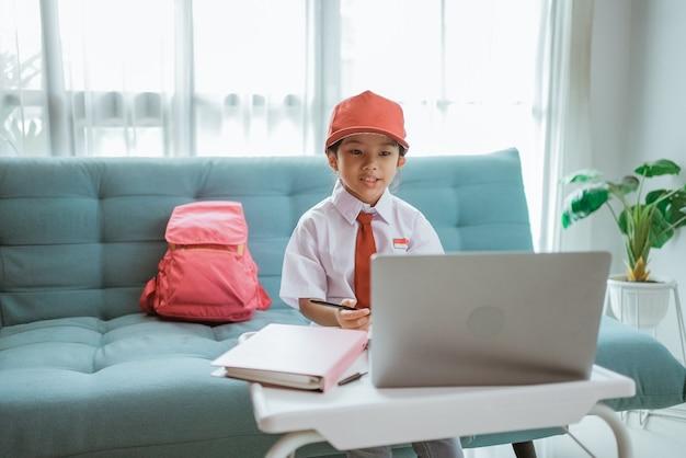 アジアの小学生がオンラインクラスの会議中に友人と教師に挨拶する