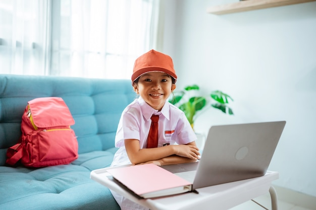 Asian primary school student looking at camera and smiling wearing indonesian school uniform during online class at home