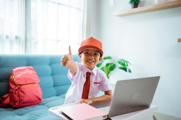 制服を着たオンラインクラスセッション中にノートパソコンを使用しているときに親指を立てるアジアの小学生