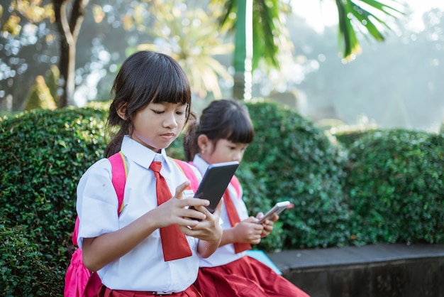 学校の公園で携帯電話を使用しているアジアの小学生