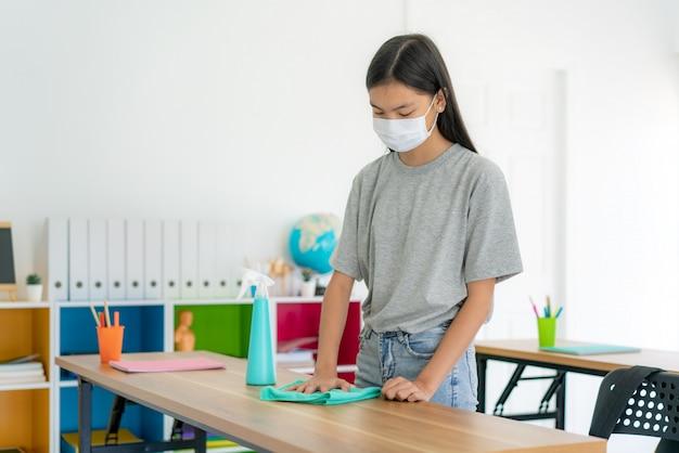 Азиатский ученик начальной школы в масках и чистящем столе салфеткой