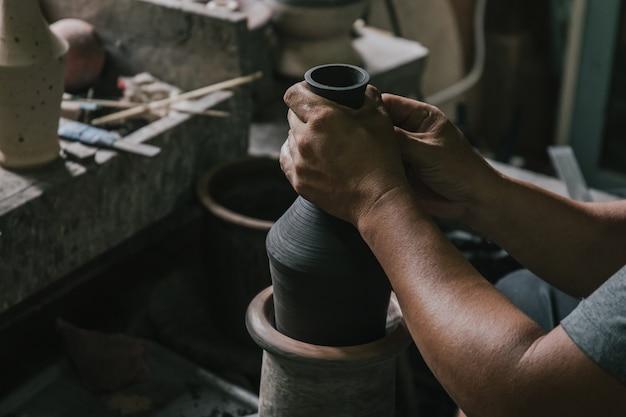 Азиатский профессиональный гончар-ремесленник, делающий художественный горшок или вазу на колесе в студии гончарной мастерской.