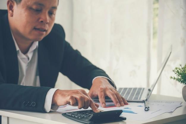 税の金融法案を数える計算機を使用してアジアのプロのビジネスマンの手