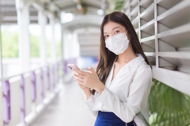 Азиатская профессиональная бизнес-леди стоит на эстакаде надземного метро в городе в маске и смотрит в камеру, используя свой смартфон для отправки сообщений в офис клиента