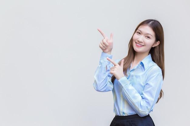 Азиатская профессиональная бизнес-леди, у которой длинные волосы с улыбкой в синей рубашке, что-то преподносит